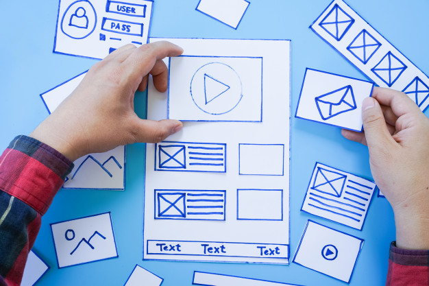 Working desk with hands sorting wireframe screens of mobile responsive website. Premium Photo