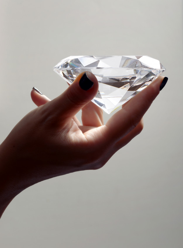 Female hand holding oversized diamond Premium Photo