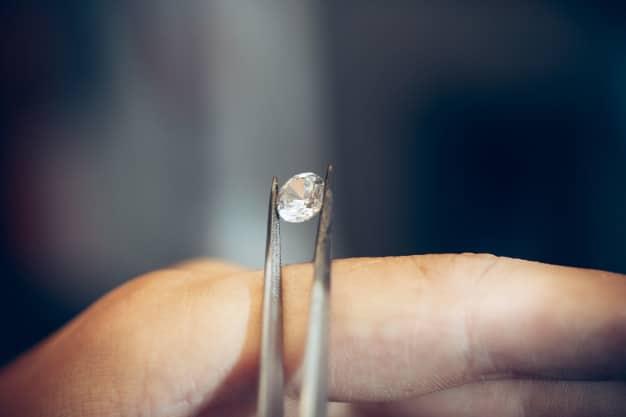 Jeweler holding diamond with tweezers Free Photo